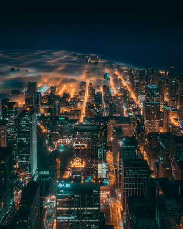 A beautiful aerial shot of the city of Chicago enveloped in fog during the night