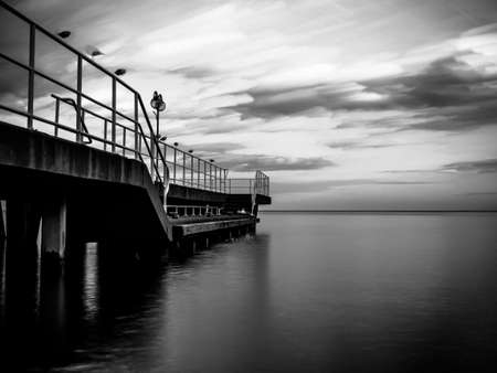 A greyscale of a sea with a bridge on it reflecting on the water under a cloudy sky Stock Photo