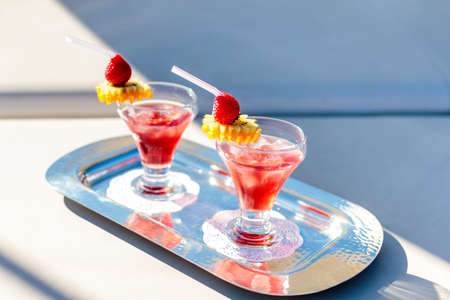 A high angle shot of red cocktails with strawberries on the tray Reklamní fotografie
