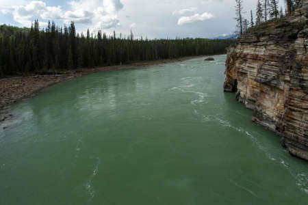 A high angle shot of the Athabasca River in Alberta Canada on a bright cloudy day Фото со стока