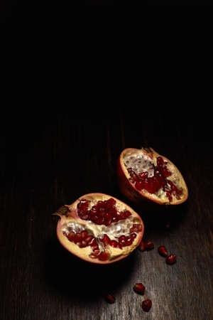 A vertical shot of two halves of a cut pomegranate on a wooden surface with a black background