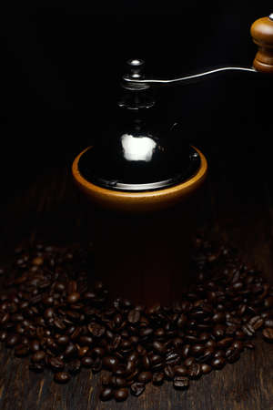 A vertical still life photography shot of a coffee grinder with coffee beans on a wooden surface