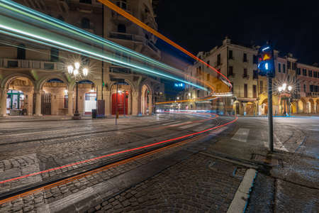 PADUA, ITALY - Apr 01, 2018: light trails left by the tram that crosses the city of Padua for the public city service at night Standard-Bild