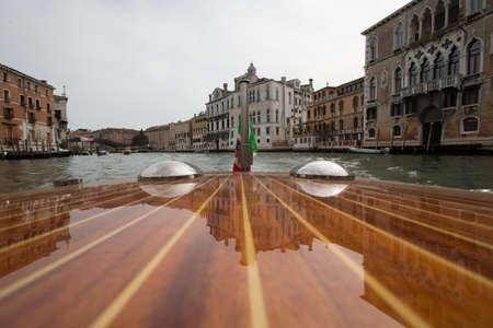 The board of a boat reflecting the buildings near the canal in Venice, Italy