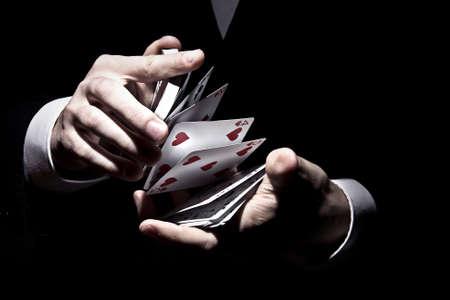 A magician shuffling the cards in a cool way under the spotlight Foto de archivo
