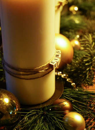 A closeup of candles surrounded by Christmas decorations against a black background