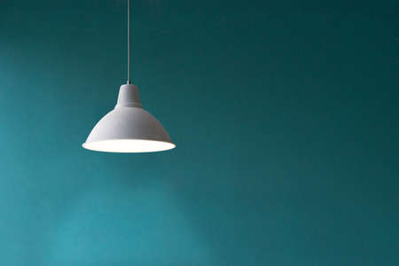 A pedant white lamp hung in front of a blue wall Standard-Bild
