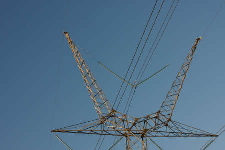 A low angle shot of an electric tower with a blue sky in the background