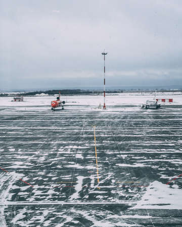 A vertical shot of a snowy airplane airstrip with  a couple of airplanes on a cloudy day