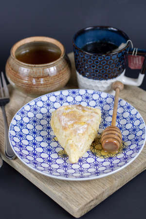 A vertical shot of a scone and honey stick on a plate with a tea on the wooden tray Imagens