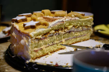 A closeup of a multilayered cake with decorations on a plate with a cake server on it 写真素材
