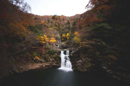 A waterfall flowing in the middle of rocky mountains in Sandankyo gorge, Japan Standard-Bild