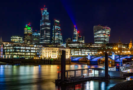 A picture of London with modern buildings and a bridge during the night with the city lights