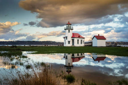The Point Robinson Lighthouse at sunset with a dramatic reflection in the water.