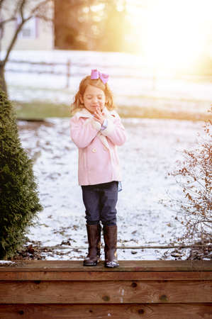 A vertical shot of the sun rising over a cute little girl praying with closed eyes