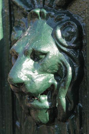 A vertical closeup shot of a gargoyle lion sign under sunlight Stock Photo