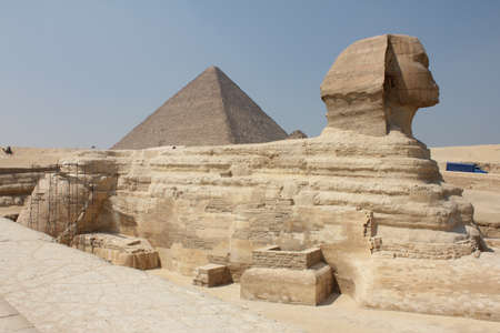 A shot of a historic sphinx in the middle of a typical Egyptian scenery under the clear sky