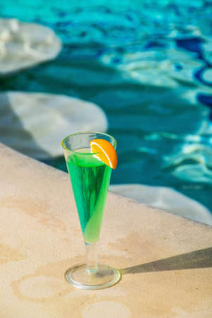 A vertical closeup shot of a green cocktail near the pool on a sunny day