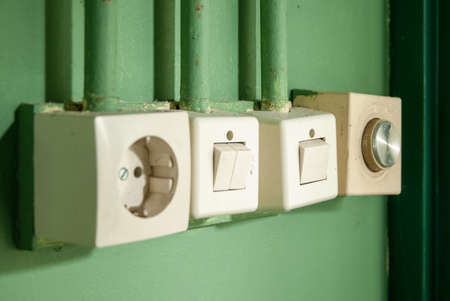 A closeup shot of light switch and light socket on a green wall