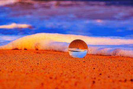 A closeup shot of a transparent sphere in an orange sandy and foamy beach during sunset Stock Photo