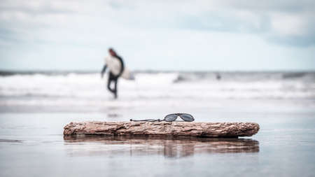 A pair of sunglasses on driftwood on the beach with a blurred background Stock Photo