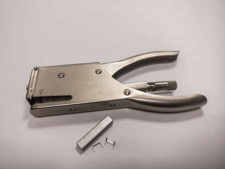 A metal staple with staple needles on a white background