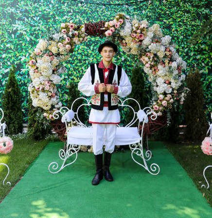 A young happy attractive male wearing traditional Moldavian clothes standing near Stock Photo