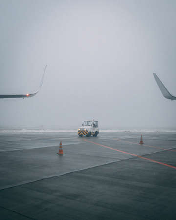 A vertical shot of an airplane runway on a moody day  with a little airport staff car