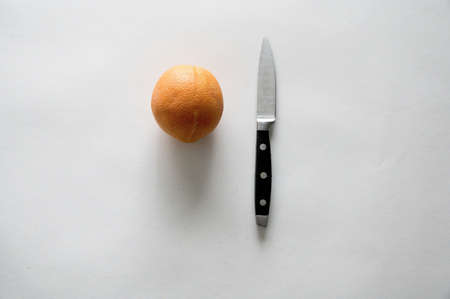A high angle shot of an orange and knife on a white surface Reklamní fotografie