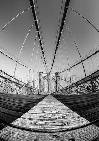A vertical greyscale shot of a suspension bridge under the clear sky