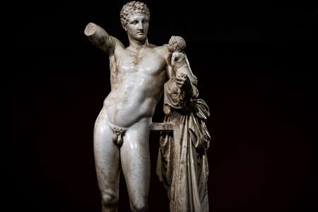 The famous Hermes by Praxiteles statue at the museum in Ancient Olympia, Greece on a black background