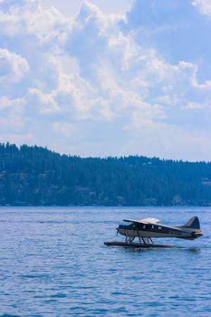 A vertical shot of a floatplane on the water with forested hills in the background under a cloudy sky