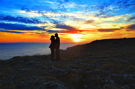 A cute couple kissing at the ocean shore under the breathtaking sunset Stock fotó