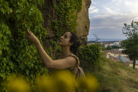 A female exploring the plants next to an ancient building Stok Fotoğraf