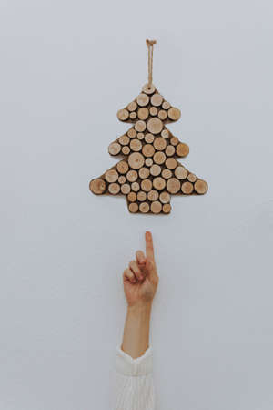 A vertical shot of a person pointing towards a Christmas decoration o the wall
