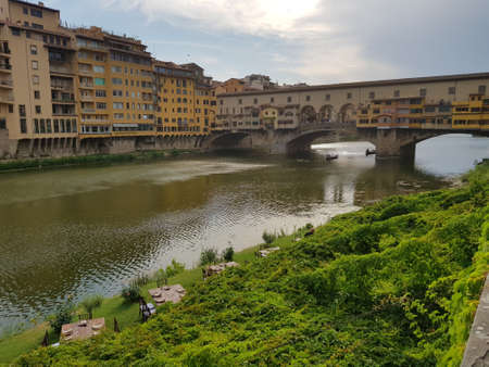 A beautiful shot of a canal in the middle of buildings with a bridge in the distance in Florence Italy