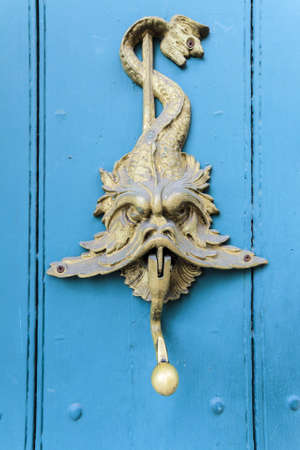 A vertical shot of a rusty doorknob with a dragon carving on a blue door