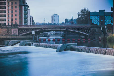 A high angle shot of a stunning waterfall flowing in the river in the middle of the city