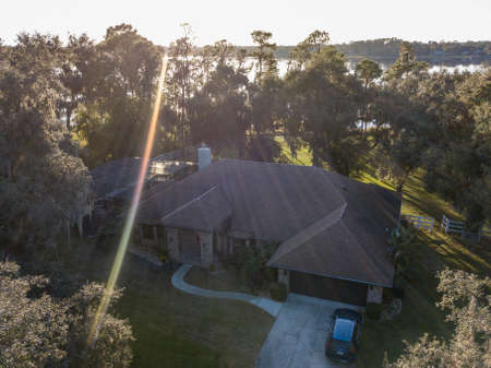 An aerial shot of a house surrounded by trees with the sun shining in the background 写真素材