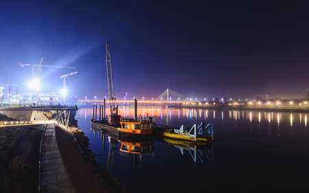View on two ships reflected in the Sava river, distant Ada bridge and Gazelle bridge at night