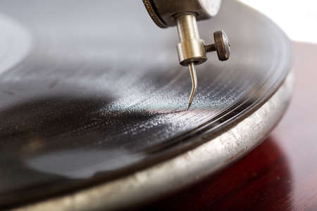 A closeup shot of a needle of the gramophone with a shellac disk