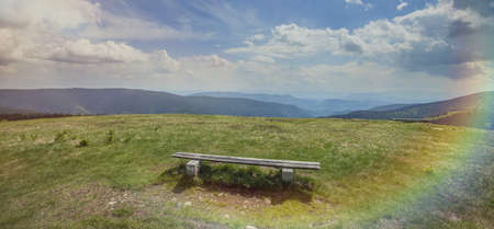 A panoramic shot of a wooden bench in the field in Charinthia, Slovenia with a rainbow on the right corner