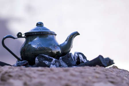 An ancient metal teapot on burning coals with a blurred background