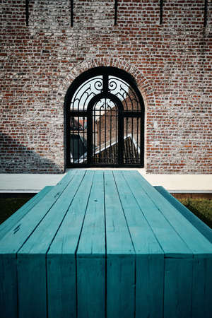 A vertical shot of a blue wooden bench in front of a building with an arch gate in Roubaix, France 免版税图像