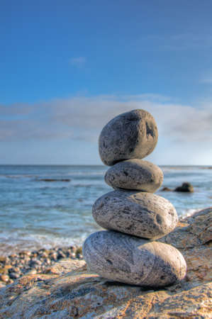 A selective focus shot of piled stones in a seashore with a blurred blue sky in the background