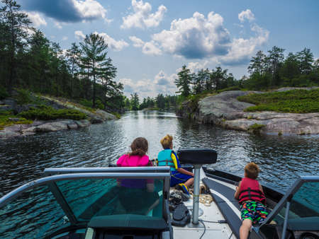 A group of kids on a boat on a river surrounded by rocks and forests under a cloudy sky
