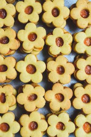 A vertical shot of many flower-shaped cookies with jam