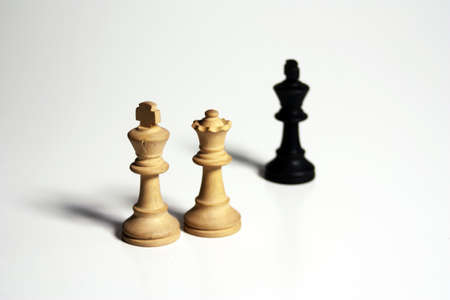 An isolated shot of two white and one black chess figures on a white background