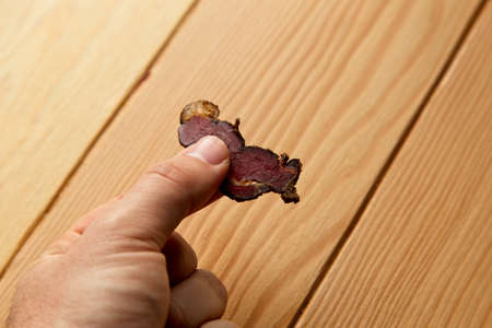 A person holding a piece of biltong with a wooden surface in the background