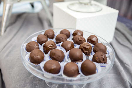 A closeup of rum balls on a plate on the table under the lights with a blurred background Фото со стока